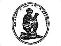 """Logo of the Abolition Committee designed by Josiah Wedgewood, showing a chained male slave on one knee holding up his hands in supplication with the words """"Am I not a man and a brother?"""""""