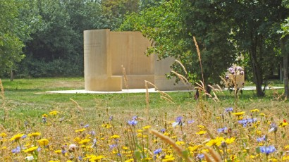 Photograph of the memorial with trees in the background and yellow and blue flowers in the foreground