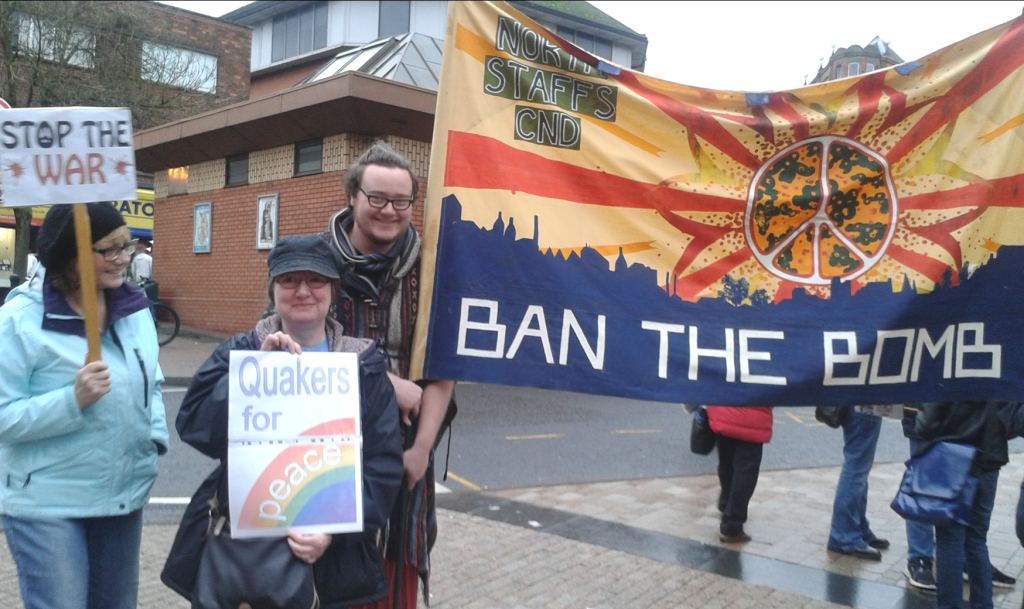 """People at a protest with banners reading """"Stop the War"""", Quakers for Peace"""" and """"Ban the Bomb"""""""