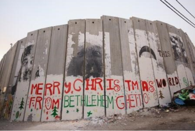 Photograph of the separation wall at Bethlehem with graffiti reading MERRY CHRISTMAS WORLD FROM BETHLEHEM GHETTO